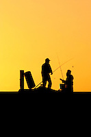 Two old fishing mates on the Cottesloe Beach groyne, the setting sun is hidden behind a rock causing the silhouette and yellow sky.