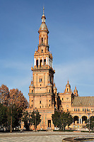 Low angle view of tower, Plaza de Espana, Seville, Spain, pictured on January 4, 2007, in the morning. Built in the Maria Luisa Park for the  Ibero-American Exposition of 1929, this huge semi-circular building, designed by Anibal Gonzalez, is a good example of Sevillian Regionalism, a combination of  Neo-Mudejar and Art Deco styles. There is a tower at each end, and a fountain in the centre of the semi-circle. Picture by Manuel Cohen.