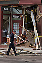 A police officer walks past storm a damaged building on Main St in downtown Springfield, MA where a tornado struck on Wednesday afternoon June 1, 2011.  (Matthew Cavanaugh for The Boston Globe)