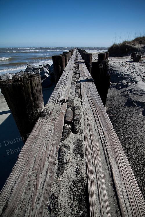 long wooden jetty pier or breakwater Folly Beach South Carolina blue sky