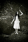 atmospheric photo of beautiful young caucasian woman lookingup in white dress standing by the lake barefoot