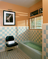 An eau-de-nil bath has been juxtaposed with blue-and-white tiles and coral pink walls