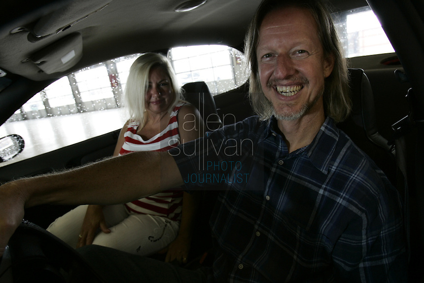 "Brooks Everett, a pastor at the Community Bible Church in Stockbridge, poses with his wife, Monica, in a car at Atlanta Motor Speedway in Hampton, Ga. on Monday, July 9, 2007. Everett won the ""Faster Pastor"" race last year at the Speedway and will try again for first place this year."