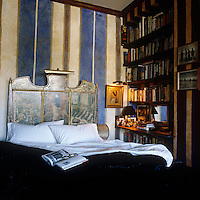 The walls of this bedroom have been painted with cream and pale indigo stripes and the headboard with dramatic scenes