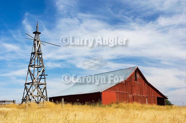Red barn in grain field, windmill tower in rural Oregon.