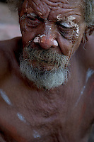 Painted face of an elder aborigine man as he contenplates during a rain ceremony on the rocks in a quiet spot outside Wyndham.