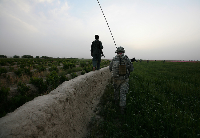 An Afghan police officer walks atop a mud wall alongside Spc. Andrew Gardiner, 29, of Gloucester, Va., a soldier with Company A, 2nd Battalion, 2nd Infantry Regiment, near the village of Mira Hor in Kandahar province, Afghanistan. April 18, 2009. DREW BROWN/STARS AND STRIPES