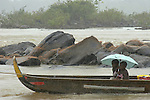 The Marowijne River, Suriname.  Children take cover under an umbrella while their dugout canoe is stuck on a rock in the rapids.