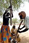 Three women displaced by violence in Sudan's Darfur region grind grain in the Abu Jabra IDP Camp.