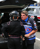 Aug. 2, 2014; Kent, WA, USA; Funny car driver Terry Haddock (right) helps dress his wife NHRA top fuel dragster driver Jenna Haddock into her safety gear during qualifying for the Northwest Nationals at Pacific Raceways. Mandatory Credit: Mark J. Rebilas-