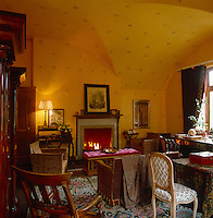 The stencilled yellow walls add to the warm atmosphere of this cosy vaulted sitting room