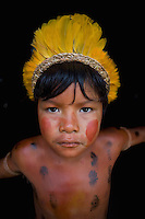 Xingu Indian boy with feather headdress and face and body paint, Amazon Bain, Brazil.