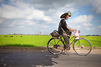 An old man rides his bike along the rapidly disappearing rice paddies in Bali Indonesia.  When I took this photo I felt his sad face told the whole story.  Development for mostly western villas is destroying an ancient way of life faster than this man can ride.