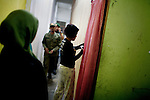 Sharia Police, or the morality police, check a brothel for pre-marital sex or adultery, in Banda Aceh,  Indonesia, on Saturday, Nov. 21, 2009. They arrest a woman prostitute who claims that she is Christian and does not need to wear a headscarf.
