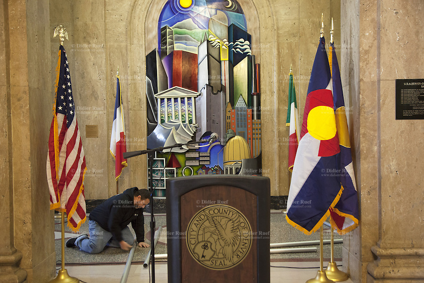 """USA. Colorado state. Denver. Worker on his knees inside the building of City and County of Denver. Four flags, Usa, Denver, France and Italy. A microphone and a stand used for media conferences. The flag of the City and County of Denver, Colorado, was designed by North Denver high school student, Margaret Overbeck, and adopted in 1926. A zigzag white stripe horizontally separates a blue field above, in which is centered a yellow circle, from a red field below, together forming a stylized depiction of the sun in a blue sky above snow-capped mountains. The color yellow symbolizes gold in the state's hills, and red the colored earth to which the word Colorado refers. The circle's centered position symbolizes Denver's central location within the state. The white zigzag symbolizes Colorado's Native American heritage. The national flag of the United States of America, often referred to as the American flag, consists of thirteen equal horizontal stripes of red (top and bottom) alternating with white, with a blue rectangle in the canton (referred to specifically as the """"union"""") bearing fifty small, white, five-pointed stars arranged in nine offset horizontal rows of six stars (top and bottom) alternating with rows of five stars. 18.12.2014 © 2014 Didier Ruef"""