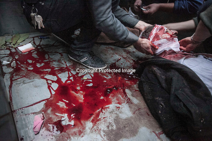 In this Monday, Dec. 03, 2012 photo, a Syrian man killed by shrapnel, is wrapped with bandages for his funeral outside of a makeshift clinic during heavy shelling in Bustan Al-Pasha district in Aleppo, the Syrian's largest city. (AP Photo/Narciso Contreras)