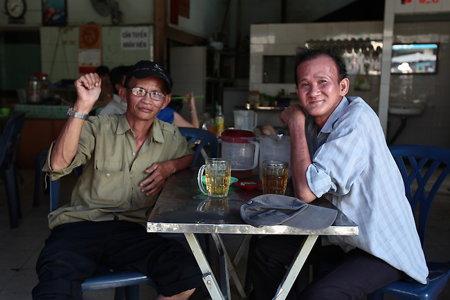 Two men drink iced beer at a restaurant near the market in District 11 in Ho Chi Minh City, Vietnam. Aug. 16, 2011.