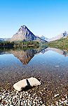 Mountains and trees are reflected in the lake at Glacier National Park.