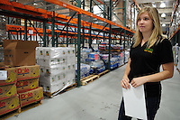 Phoenix, Arizona. October 18, 2012 - Britany Statt -United Food Bank Marketing Director- observes the operations of the food bank's warehouse. She explained that Arizona is tied as the worst state in the U.S. When it comes to child hunger. As the amount of food donations decreases, food banks such as the United Food Bank strive to keep up with hunger relief needs of 1 in 5 (20%) of Arizonans who are living in poverty and, based on figures of the Department of Health and Human Services. Photo by Eduardo Barraza © 2012