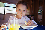 Young girl ( 7 years old) in bed with flu/cold eating crackers and looking miserable into camera.       MR