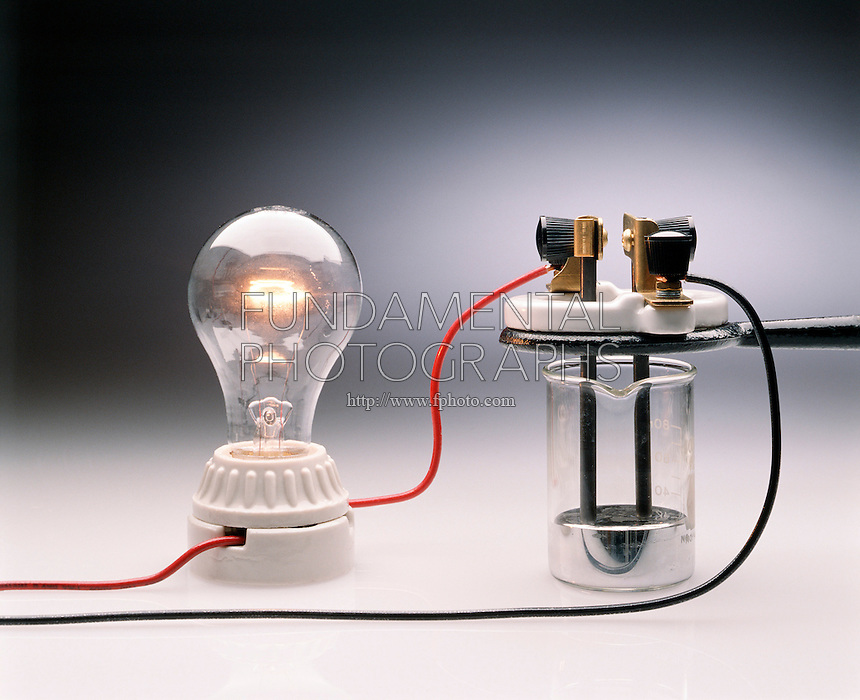 CONDUCTIVITY TEST: MERCURY<br /> Demonstrating A Simple Circuit<br /> Apparatus demonstrates a simple circuit incorporating mercury and electrodes of carbon. The glowing light bulb shows that mercury, as well as carbon, conducts electricity.