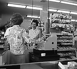 """Bethel Park PA:  View of woman at the check out counter of Bethel Market Grocery Store.  Marjorie Stewart is being checked out by Millie during an onsite photography assignment for Bethel Market.  Bethel Market was """"the"""" grocery store in Bethel Park from the late 1950s through the early 1980s."""
