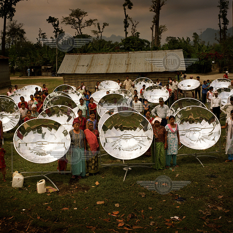Local residents with their new solar cookers at a Bhutanese refugee settlement. With the financial help of the Dutch Council for Refugees, a total of 6,300 solar cookers will be distributed amongst the Bhutanese refugees living in the region. The solar cookers consist of a reflective, aluminium, parabolic-shaped device that concentrates the sun's rays onto cooking pots placed on a frame in the centre of the dish. The dish has to be adjusted to the new position of the sun around every 10 minutes. It takes about 55 minutes to prepare a cooked meal on a sunny day and it is hoped that using the solar cookers will alleviate pressure on resources and reduce kerosene consumption by 75%.