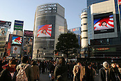 A female sailor from the 'Marine Self Defence Force', of Japan, stands in front of the rising sun flag of Japan, in a promotional video for the Marines Force, which plays on 3 screens above the streets of the Shibuya district...