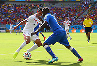 Mario Balotelli of Italy is tackled by Giancarlo Gonzalez of Costa Rica
