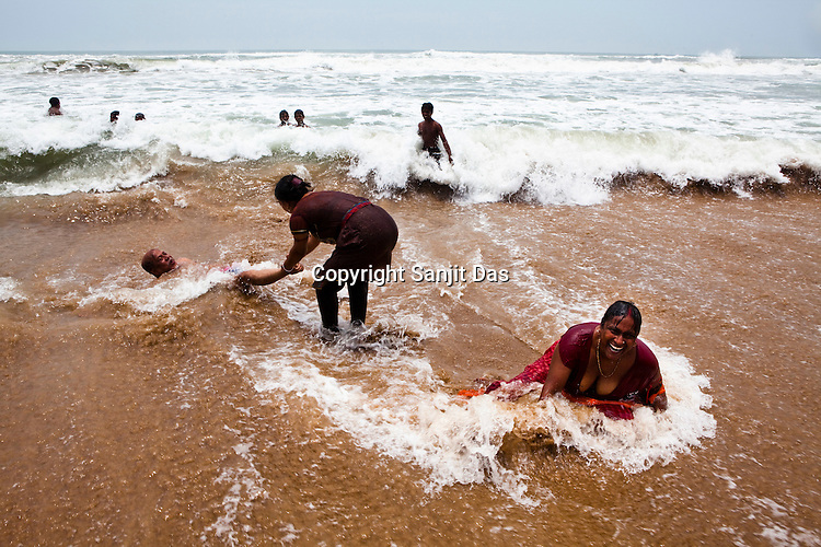 A young woman holds her fathers' legs as he is dragged towards the sea on the shores of Puri Beach along the Bay of Bengal in Puri, Orissa, India. A dip in its salty waters is believed to hold great religious significance, as a result these golden sand beaches sees is a never-ending rush of pilgrims and tourists. Photo: Sanjit Das/Panos