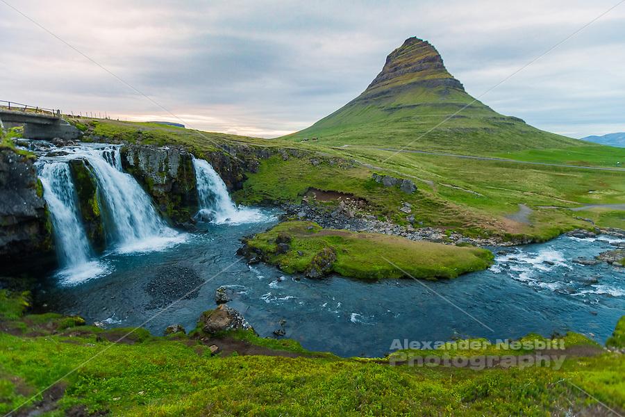 Kirkufellfoss - waterfall flows around the loan  pyramidal mountain Kirkufell on the Snaefellesness Pennisula of Iceland