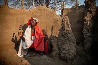 Witchdoctor Paulino Conselho (52) squats in his 'hospital' hut that was destroyed by a tornado.