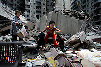 Beirut, Lebanon, Aug 14 2006.Zeina, 11, searches the rubble for family belongings with her mother Mariam Hassan Jinah and her father Khalil Tawil, 52. Their home was an appartment on the 9th floor of an 11 storey building, completely levelled by an Israeli air raid. Mere hours after the beginning of the cease-fire, thousands of inhabitants return to Hareit Hreik, the main Hezbollah stronghold in the capital, constantly targeted by Israeli air force bombing raids during 33 days and almost totally destroyed as a result.