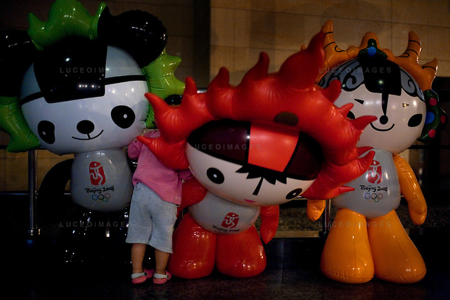 A little girl gets lost amongst giant inflatable Olympic mascots in Beijing, China on Thursday, August 21, 2008.  Kevin German