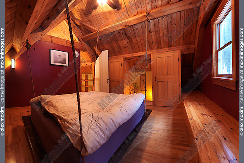 Attic loft bedroom with a hanging bed in a Canadian timberframe country house, interior with a lot of wood, Muskoka, Ontario, Canada