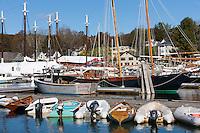 Dinghies line a dock in front of schooners and windjammers anchored in Camden harbor in Camden, Maine