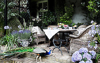 The covered terrace is furnished with rattan chairs and filled with tubs of lavender and scented flowers