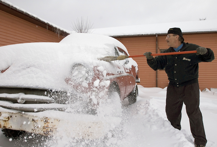 "Jim ""Hoolie"" DeCaire, owner of ""Da Yooper's Tourist Trap and Museum"" in Ishpeming, Mich. sweeps snow from a vehicle at the museum."