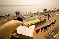 Man hanging out the washing with the wallahs working on the banks of the Ganges in the background.<br /> (Photo by Matt Considine - Images of Asia Collection)