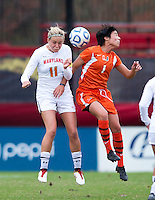 Kate Howarth (1) of Miami goes up for a header with Olivia Wagner (11) of Maryland during the game at Ludwig Field in College Park, MD.  Maryland defeated Miami, 2-1, in overtime.