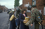 Belfast The Troubles. 1980s. British soldiers stop and search woman and daughter.