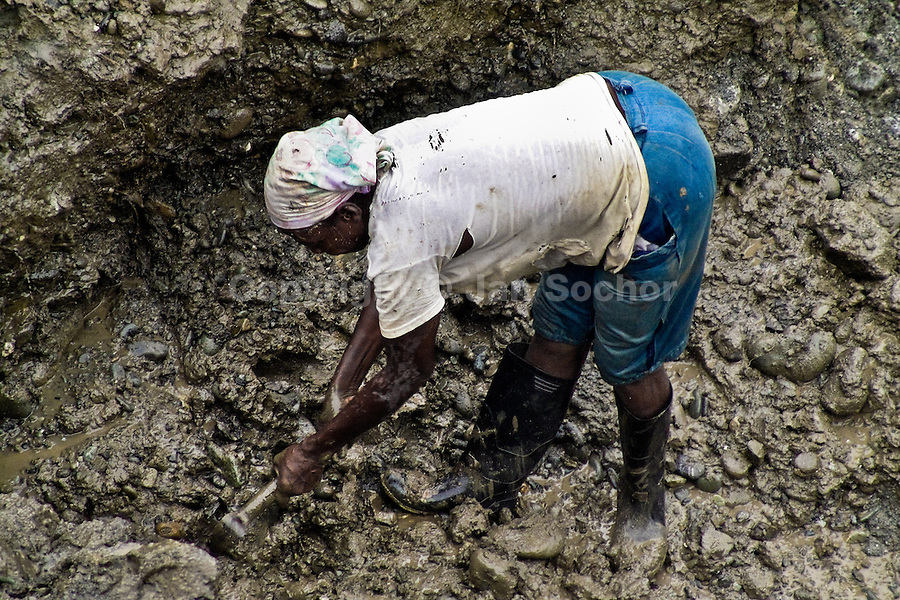 A Colombian woman miner diggs the goldbearing mud in the Remolino opencut near Tadó, Chocó dept., Colombia, 25 May 2004. Chocó is a no man's land. The large inaccessible rainforest jungle area in the western lowlands of Colombia is mainly inhabited by Afro Colombian population, descendents of African slaves. High presence of malaria, guerilla drug traffic routes, tropical deseases and only an irregular river transport makes this region virtually lost. Gold that is found in the jungle rivers of Chocó is the only hope for many although they never find what they dream about.