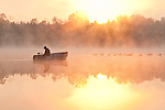 Sunrise in fog Lake Cassidy with fisherman in small fishing boat