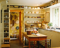 The walls of the kitchen in Nicky Haslam's Jacobean hunting lodge are lined with shelves of crockery and wicker baskets