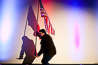 A worker moves an American flag before the Veterans for a Strong America presidential forum on Saturday, December 10, 2011 in Des Moines, IA.