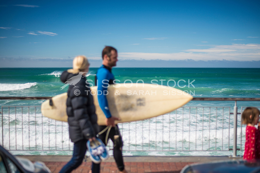 Surfer (defocused) and friend , walk on esplanade at St Clair beach on a blue sky day, Dunedin, Otago, South Island, New Zealand- stock photo, canvas, fine art print