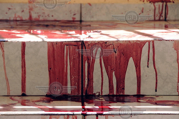 Blood on the stairs of an apartment block where a man was murdered in front of his wife.. ..