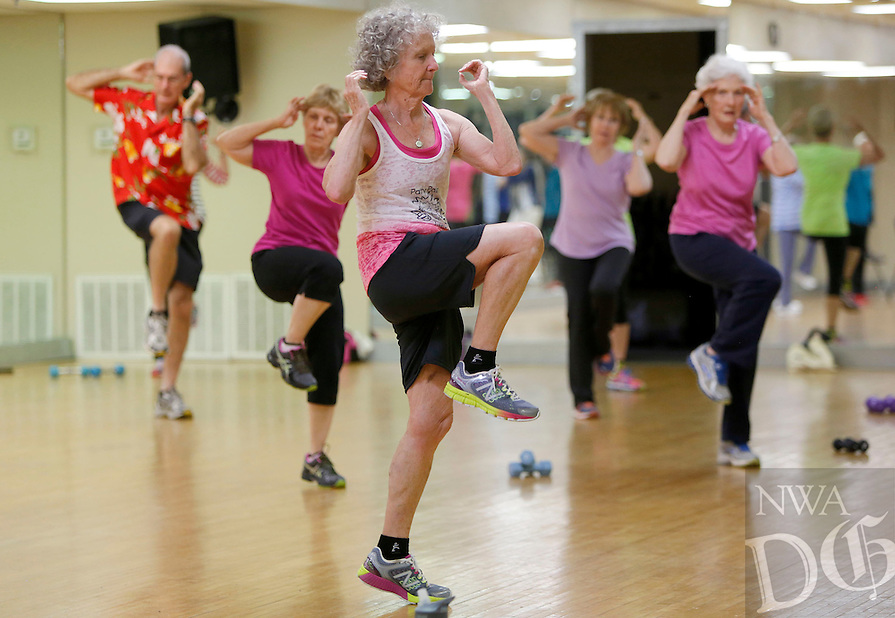 NWA Democrat-Gazette/DAVID GOTTSCHALK - Carole Swope (center), participates in Young at Heart fitness class at the Fayetteville Athletic Club Monday, July13 , 2015 under the direction of personal trainer Reuben Reina.