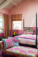 The girl's four poster bed is covered in multi-coloured and patterned bedding and cushions and has a bright upholstered chaise longue sitting at its foot