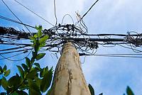 "Illegal electric connections, known as ""gato"" ( cat ), usually found in Brazilian favelas. Baixada Fluminense, Rio de Janeiro, Brazil. Antique wooden lamppost."